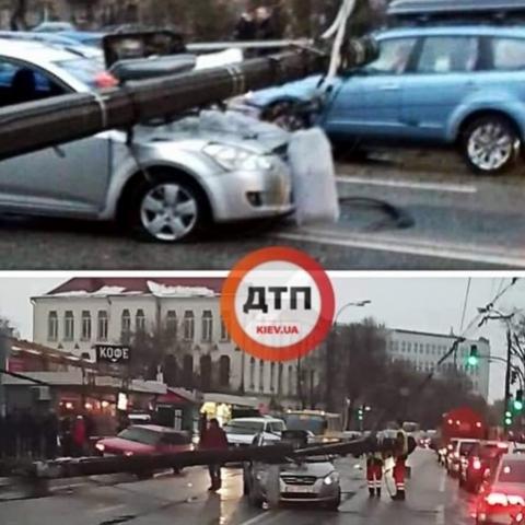 В Киеве столб рухнул на проезжавшую по дороге машину. Видео